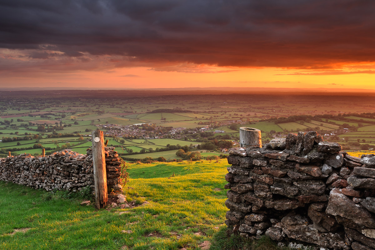 A fiery sunset breaks underneath storm clouds at Cook's Fields on the Mendip hills, Somerset. Image © Stephen Spraggon.
