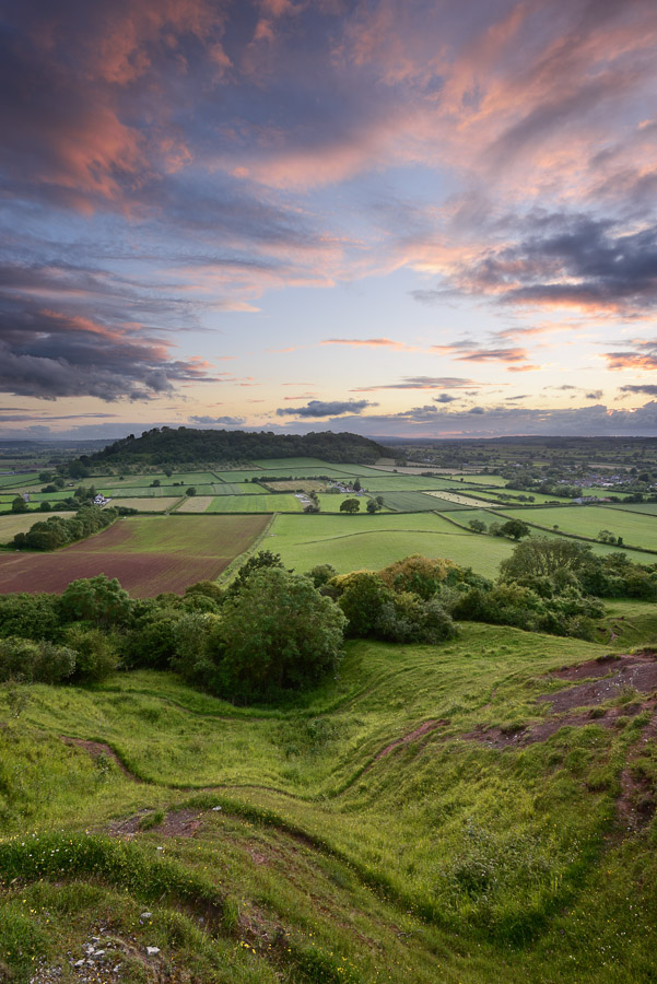 A wonderful sunset over Dundon Hill with the Somerset Levels stretching out beyond. Compton Dundon, Somerset, UK. Image © Stephen Spraggon.