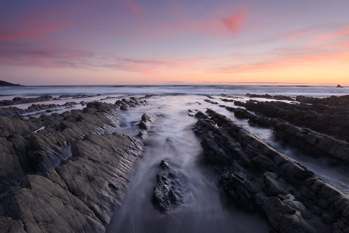 Jagged rocks leading out to sea at Welcombe Mouth, North Devon, UK. Image © Stephen Spraggon.