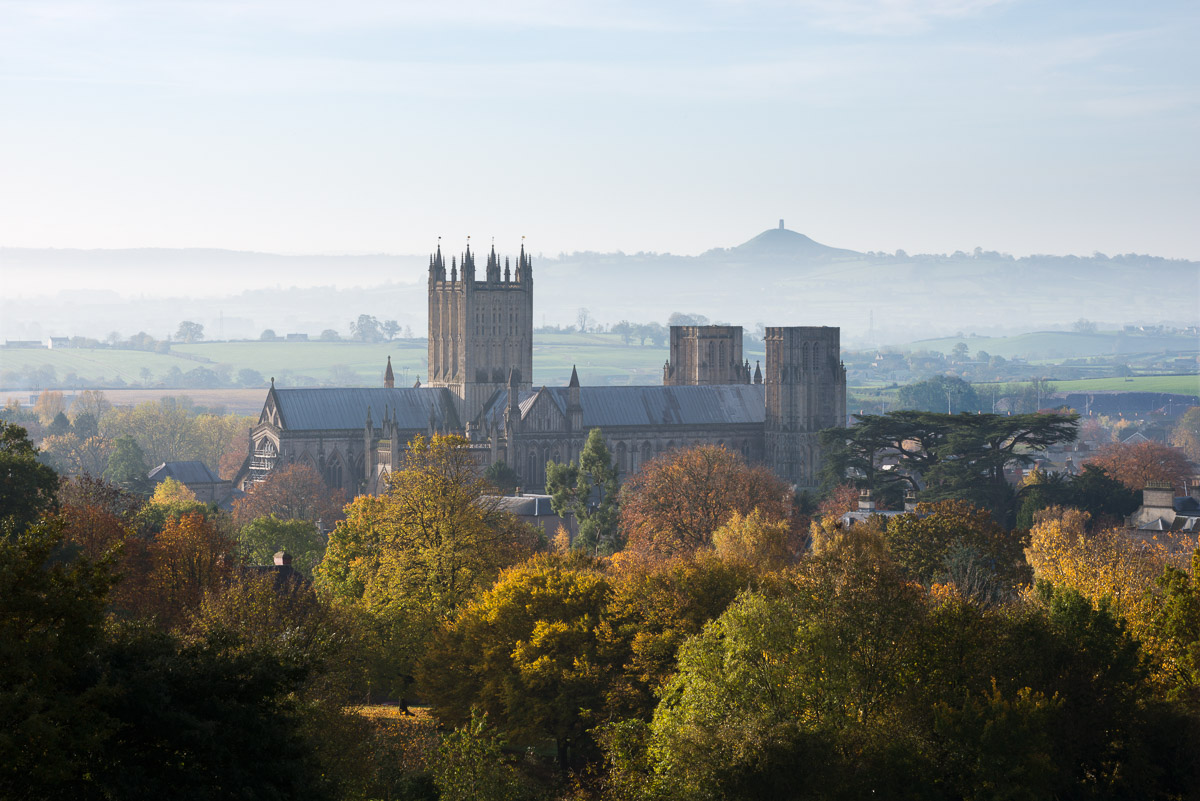 Wells Cathedral surrounded by autumnal trees on a misty morning with Glastonbury Tor visible in the distance. Wells, Somerset, UK. Image © Stephen Spraggon.