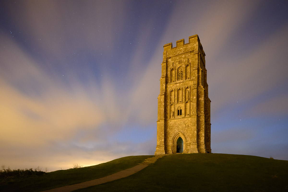 Glastonbury Tor, Somerset, illuminated by the warm glow of street lighting from the nearby town on a cloudy night. Image © Stephen Spraggon.