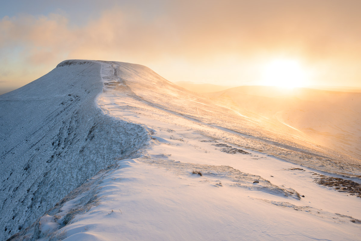 A golden sunrise lighting snow at Pen Y Fan in the Brecon Beacons, Wales.