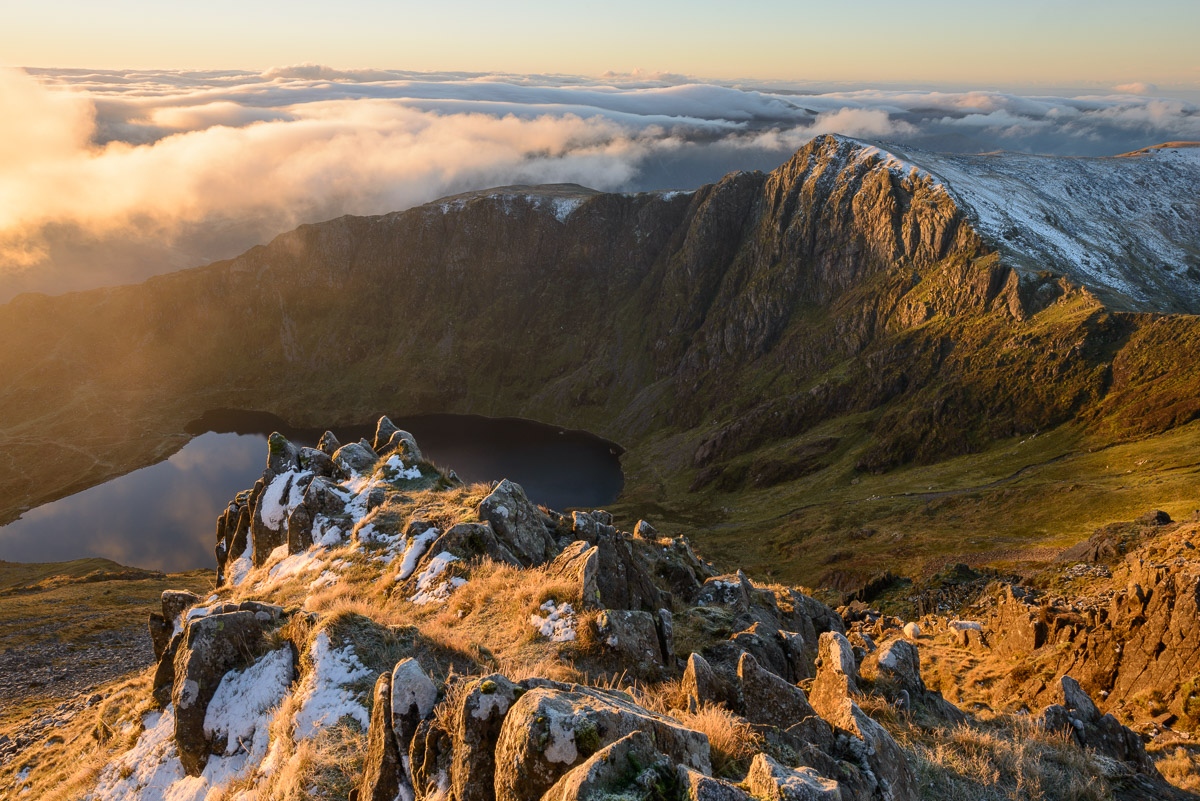 Morning light illuminates the top of Craig Cau during a cloud inversion, photographed from the top of Cadair Idris, Snowdonia. Image © Stephen Spraggon.