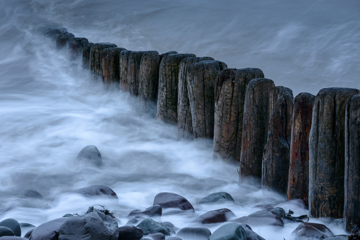 A row of wooden groynes on the beach at Porlock, Somerset, as the incoming tide washes over them. Image © Stephen Spraggon.
