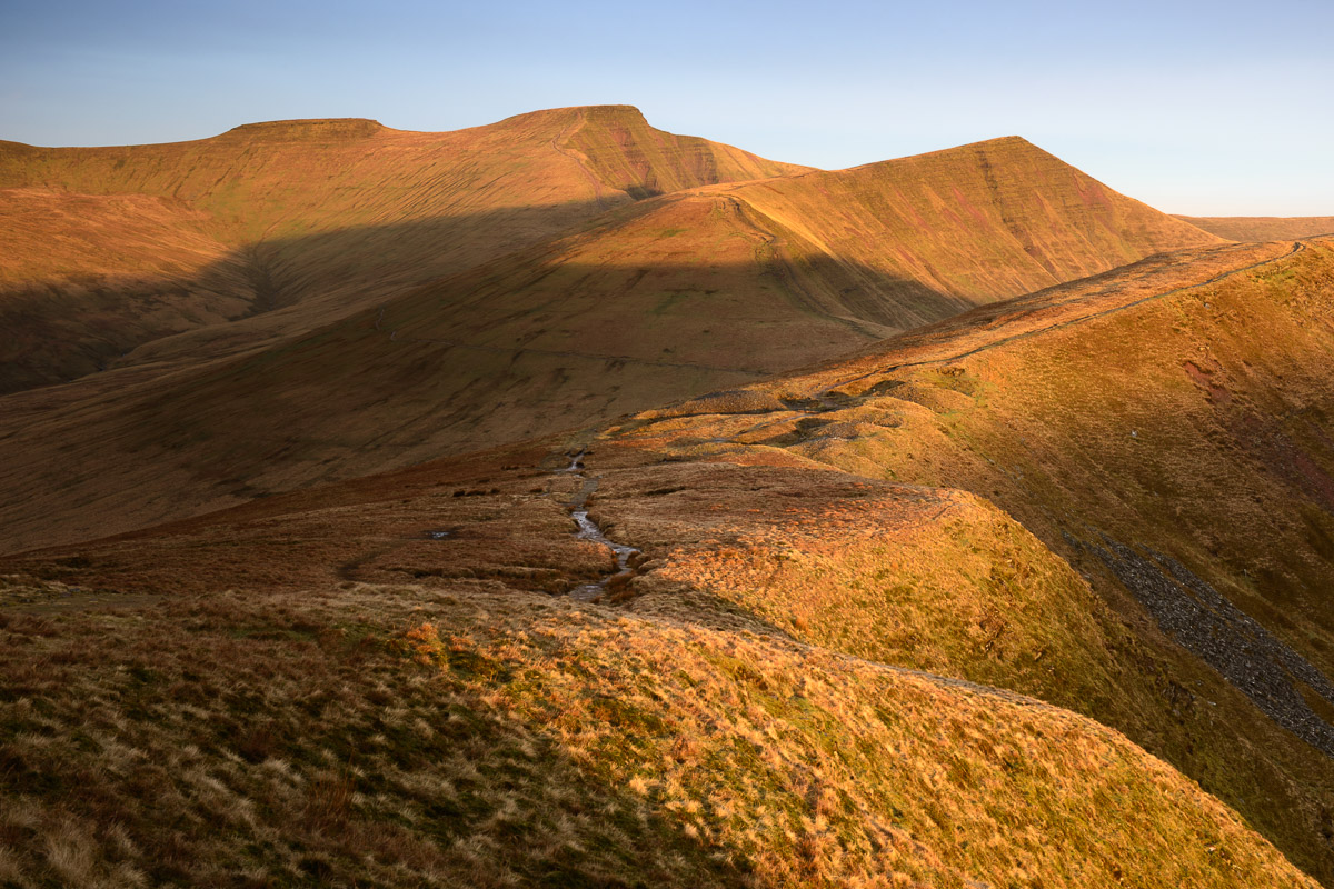 Corn Du, Pen y Fan and Cribyn, the main peaks of the Brecon Beacons, Wales, as the morning sun skirts across their peaks.. Image © Stephen Spraggon.