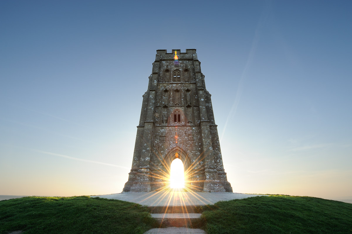 St Michael's tower atop Glastonbury Tor, Somerset, with the rising sun visible through the tower's archway. Image © Stephen Spraggon.